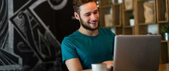 Homme à la recherche d'un ordinateur portable heureux