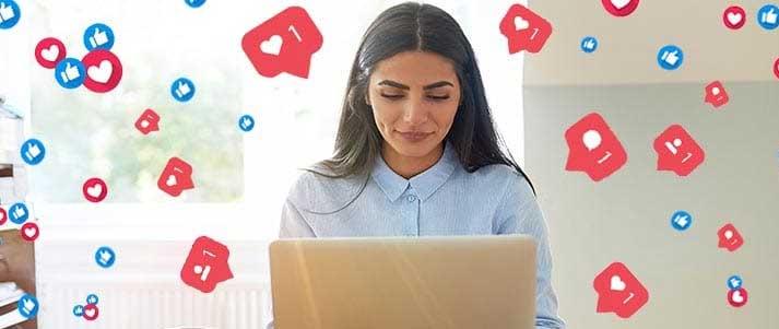 Femme sur ordinateur portable avec les médias sociaux aime et aime