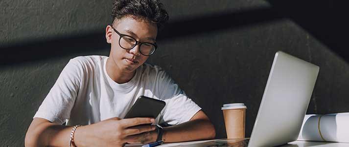 étudiant sur téléphone par ordinateur portable