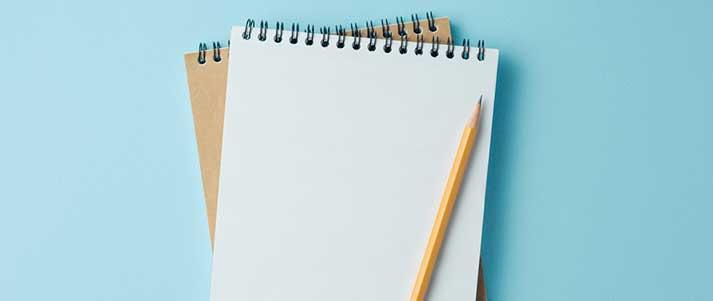 Cahiers et crayon sur fond bleu